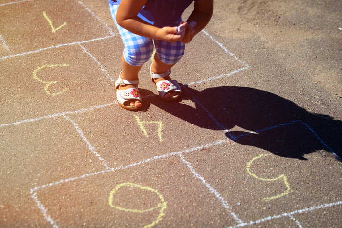 young child playing hop scotch
